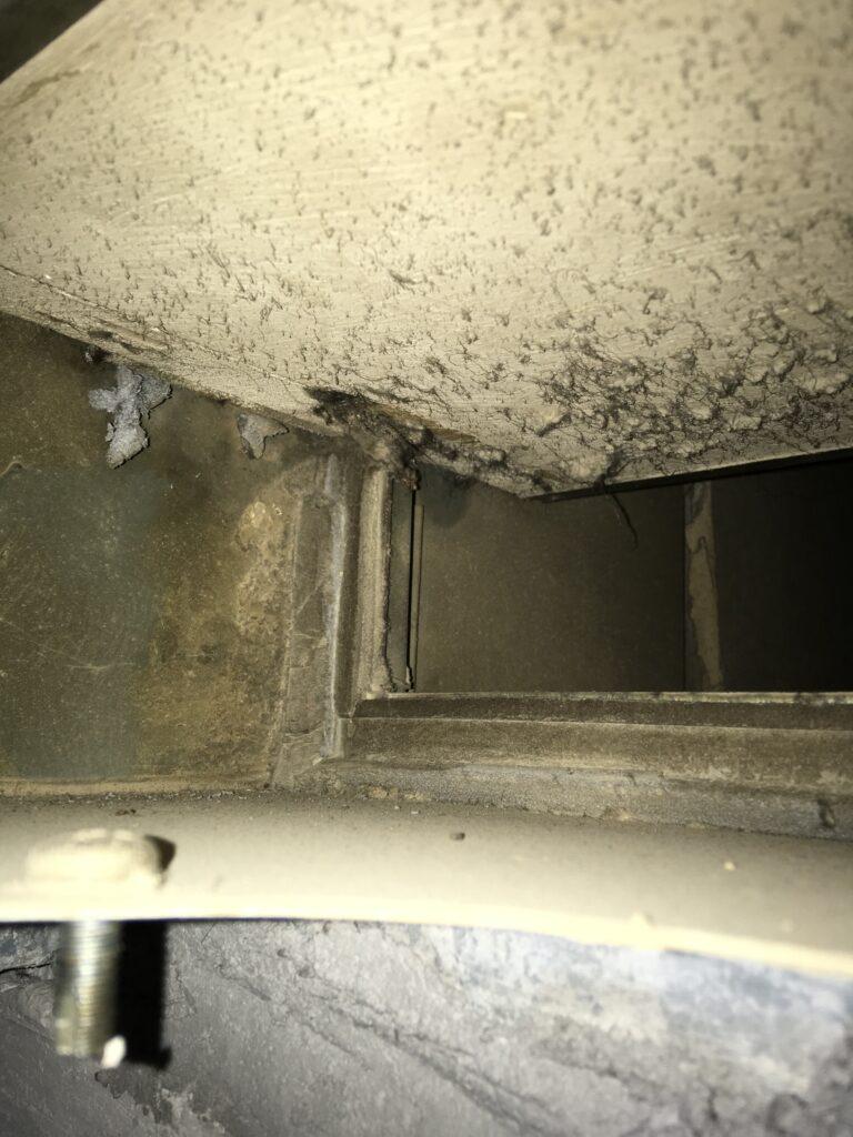Durch Auslösung des Klappenblattes verursachte Ablösung von Asbestschaumstoff